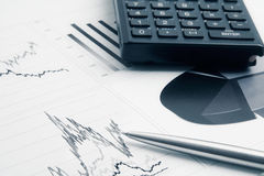 Business background. With finance graphs, pen, and calculator Stock Photo