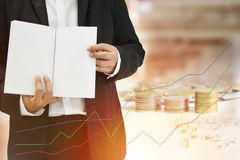 Business background blur of asian aged 40 to standing in black suit and gesture holding white paper golden ,silver and Graphs. Stock Photo