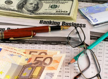 Business background. With dollars, euros, documents, glasses, pen Stock Image
