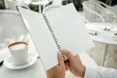 Business background hand of businessman hold blank notebook pape. R with coffee and copy space. image for education, food, diary, document, body, object concept Royalty Free Stock Image