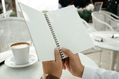 Business background hand of businessman hold blank notebook pape. R with coffee and copy space. image for education, food, diary, document, body, object concept Stock Photo