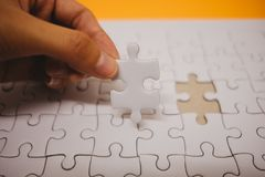 Business background hand of businessman pick one piece jigsaw pl Royalty Free Stock Photos