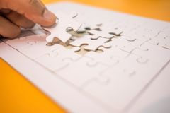 Business background hand of businessman pick one piece jigsaw pl. Aced on orange table with copy space. image for texture, problem, thinking, idea, toy, puzzle Royalty Free Stock Photos