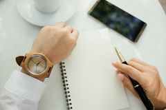 Business background hand of businessman wearing wooden watch wit. H pen, notebook, coffee, mobile phone on table. image for technology, education, fashion Stock Photography
