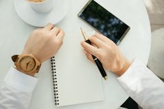 Business background hand of businessman wearing wooden watch wit. H pen, notebook, coffee, mobile phone on table. image for technology, education, fashion Stock Photo