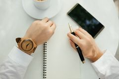 Business background hand of businessman wearing wooden watch wit. H pen, notebook, coffee, mobile phone on table. image for technology, education, fashion Royalty Free Stock Photography