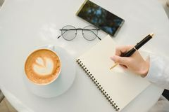 Business background hand of businessman write notebook paper wit. H coffee, glasses, mobile phone, copy space. image for technology, beverage, idea, equipment Royalty Free Stock Photo