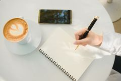 Business background hand of businessman write notebook paper wit. H coffee, mobile phone, copy space. image for technology, beverage, idea, equipment, cafe Royalty Free Stock Photography