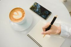 Business background hand of businessman write notebook paper wit. H coffee, mobile phone, copy space. image for technology, beverage, idea, equipment, cafe Stock Photo