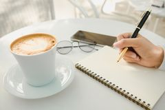 Business background hand of businessman write notebook paper wit. H coffee, glasses, mobile phone, copy space. image for technology, beverage, idea, equipment Stock Image