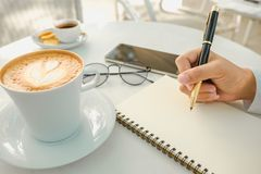Business background hand of businessman write notebook paper wit. H coffee, glasses, mobile phone, copy space. image for technology, beverage, idea, equipment Stock Photo