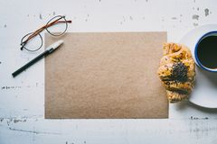 Business background for letter writing.Mock-up blank craft sheet of empty paper, pen, eye glasses and morning coffee cup. With croissant on white wooden desk Royalty Free Stock Photography