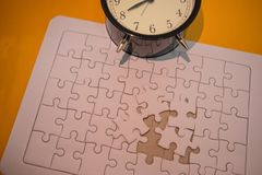 Business background white jigsaw placed on orange table with clock and copy space. image for texture, problem, thinking, idea, to. Y, time, success, game concept royalty free stock image