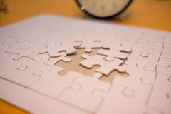 Business background white jigsaw placed on orange table with clock and copy space. image for texture, problem, thinking, idea, to. Y, time, success, game concept royalty free stock photos