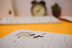 Business background white jigsaw placed on orange table with clock, keyboard and copy space. image for texture, problem, thinking. Idea, toy, time, workspace royalty free stock images