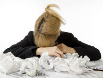 Business is bad!. Business woman is dismayed with her head down in pile of paperwork Royalty Free Stock Photos