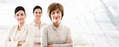 Business banner - three businesswomen. Happy team of three businesswomen standing in front of windows inside officebuilding, smiling. Business banner royalty free stock images
