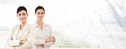 Business banner - two businesswomen. Happy businesswomen standing in front of windows inside officebuilding, smiling. Business banner royalty free stock photography