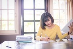 Business beautiful Asian woman working and writing note. Business beautiful Asian woman working and writing in coffee shop Stock Images