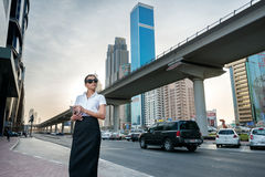 Business in the big city. Successful arabic businesswoman standi. Ng in the street in formal attire. Businessman standing near skyscrapers in Dubai downtown in Stock Photo