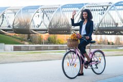 Business black woman riding a vintage bicycle in the city royalty free stock photo