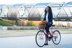 Business black woman riding a vintage bicycle in the city royalty free stock photography