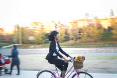 Business black woman riding a vintage bicycle in the city royalty free stock images