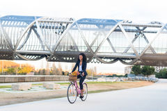 Business black woman riding a vintage bicycle in the city stock photos