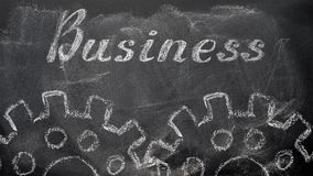 Business. The blackboard writing with chalk and the concept of business and finance, the text `Business`, and two chalk silhouette drawing gears Stock Illustration