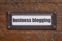 Business blogging label. Business blogging - file cabinet label, bronze holder against grunge and scratched wood stock image