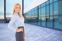 Business blond woman standing on street against modern building Stock Images