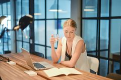 Business blonde girl drinking water in front of a laptop.  stock image