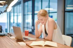 Business blonde girl writing a book and phoning in front of a la. Ptop Stock Photo