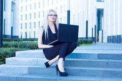 Business blonde with red lips sitting and working with laptop Royalty Free Stock Images