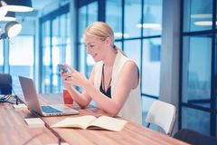 Business blonde woman using a phone in front of a laptop stock photography