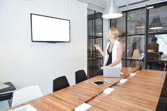 Business blonde woman watching TV with blank screen in office.  Stock Photography