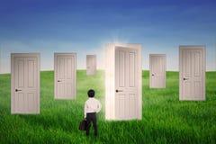 Business boy standing in front of opportunity doors. Outdoor Stock Image