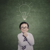 Business boy thinking on drawn lamp background Stock Image