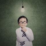 Business boy thinking gesture under lit bulb Stock Image