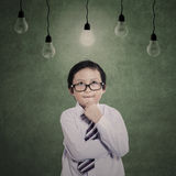 Business boy thinking under lamps Stock Image