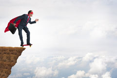 Business bravery courage concept. Superhero businessman leaping off a cliff on a skateboard stock photo