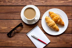 Business breakfast with coffee and croussant top view. Business breakfast with coffee, croussant on wooden table top view stock photos