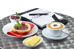 Business breakfast. A fresh sesame roll with cherry jam and a cup of cappuccino; a personal organizer in the background stock photos