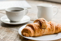 Business breakfast in office with coffee, milk and croissant on wooden table background. Business breakfast in office with cup of coffee, milk and croissant on royalty free stock photography