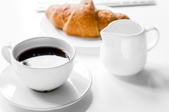 Business breakfast in office with milk, coffee and croissant on. Business breakfast in office with milk, cup of coffee and croissant on white table background Stock Images