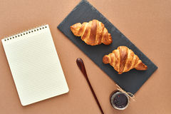 Business breakfast of two French croissants with notepad. Flat composition of two croissants with jam, wooden spoon and notepad on brown craft paper background Royalty Free Stock Images