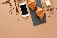 Business breakfast of two French croissants with smartphone. Flat composition of two croissants with coffee beans, butter, wooden spoon and smartphone on brown Stock Image