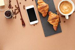 Business breakfast of two French croissants with smartphone. Flat composition of two croissants with cup of coffee, jam, coffee beans, wooden spoon and Stock Photos
