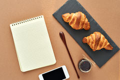 Business breakfast of two French croissants with smartphone. Flat composition of two croissants with jam, wooden spoon, notepad and smartphone on brown craft Royalty Free Stock Photos