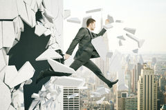 Business breakthrough. Success concept with man jumping through wall on city background royalty free stock images
